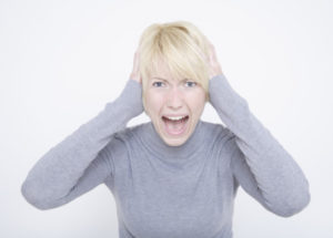 Portrait of young woman shouting against white background, close up
