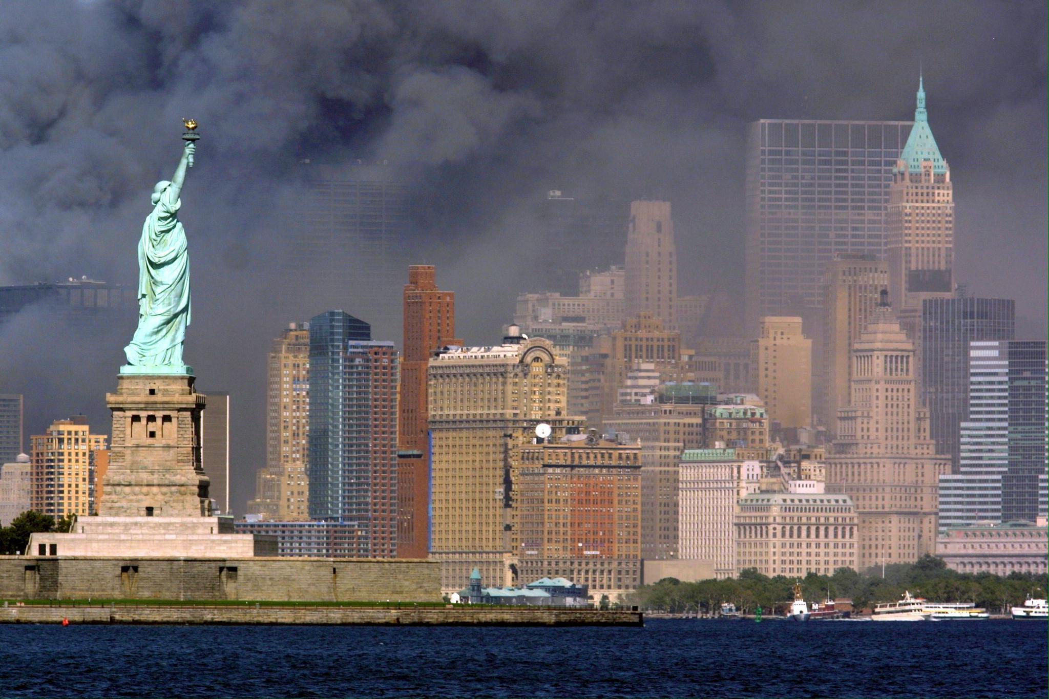 Un momento del crollo delle Torri Gemelle visto da dietro la Statua della Libertà.