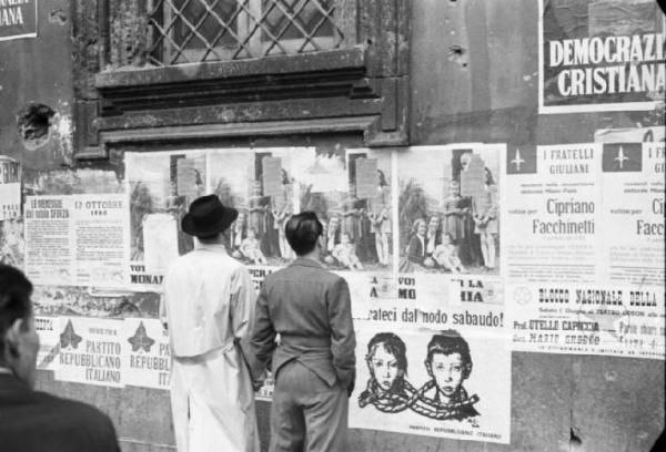 Alcuni cittadini leggono un manifesto DC nel 1985 a Catania.