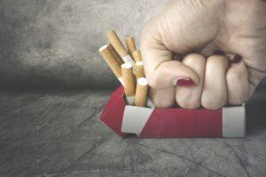 Woman fist crushing cigarettes