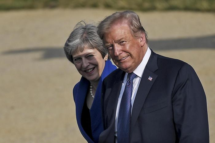 epaselect epa06881806 US President Donald J. Trump (R) and British Prime Minister Theresa May (L) smile as they arrive for a family photo in front of the Arcades du Cinquantenaire during a NATO Summit in Brussels, Belgium, 11 July 2018. NATO member countries' heads of states and governments gather in Brussels on 11 and 12 July 2018 for a two days meeting. EPA/CHRISTIAN BRUNA