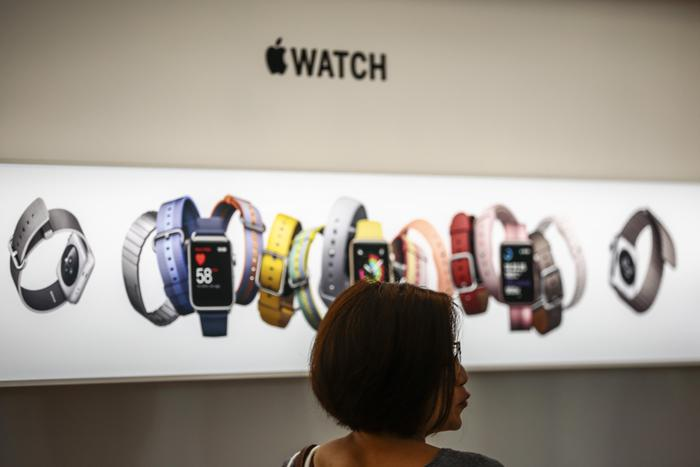 epa06218679 A woman pictured against an Apple watch display at the Apple Orchard store in Singapore, 22 September 2017. The iPhone 8, iPhone 8 Plus and iPhone X were announced by tech giant Apple as the latest iterations of their iconic mobile devices. EPA/WALLACE WOON