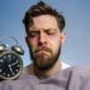 Closeup, man looking angry at the alarm clock , insomnia concept