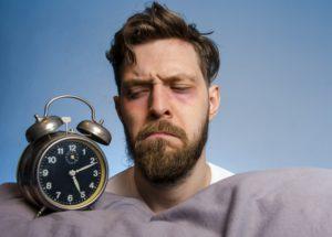 Closeup, man looking angry at the alarm clock , insomnia concept